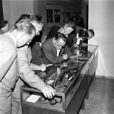 """Dokumenty zvířeckého činu teroristů v Babicích na výstavě """"30 let KSČ"""". Ve třech skleněných skříních jsou zde vyloženy jak americké, tak německé zbraně, granáty a třaskavinové nálože, tak i růžence a jiné předměty, nalezené u zneškodněných vrahů, kteří zabíjeli v žoldu amerických imperialistů. Dobový text, červenec 1951 (zdroj: ČTK)"""