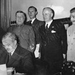 Lidový komisař zahraničních věcí Vjačeslav Molotov dne 28. září 1939 v Moskvě podepisuje sovětsko–německou smlouvu o přátelství a hranicích, na základě které připadly Německu Poláky osídlené oblasti Běloruska a Ukrajiny. Sovětský svaz výměnou získal Litvu. V pozadí Stalin a německý ministr zahraničí von Ribbentrop.