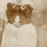 Fotografie stařenky sedící na křesle před gruntem